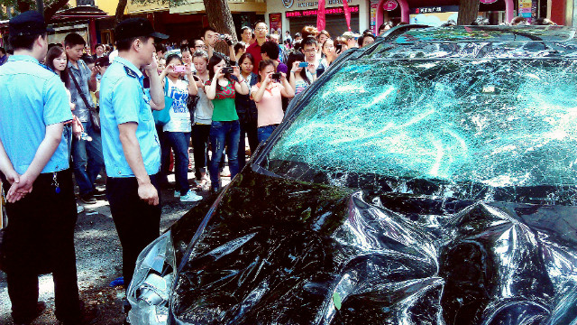 People take pictures of a Japanese car damaged during a protest against Japan's 'nationalizing' of the disputed Diaoyu Islands, also known as Senkaku Islands in Japan, in the Chinese city of Xi'an, on September 15, 2012.