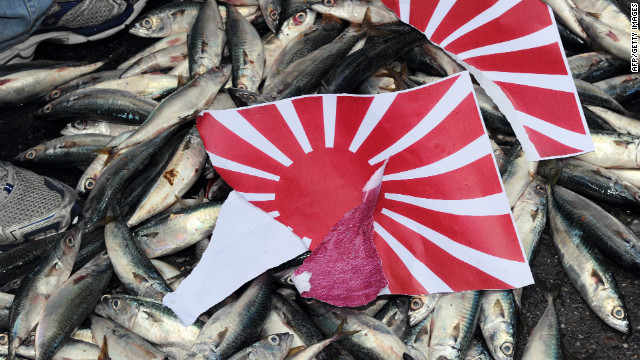 A torn apart Japanese 'Rising Sun' flag is placed on dead fish during a demonstration in Taipei on September 14, 2010, over the disputed Senkaku/Diaoyu island chain.