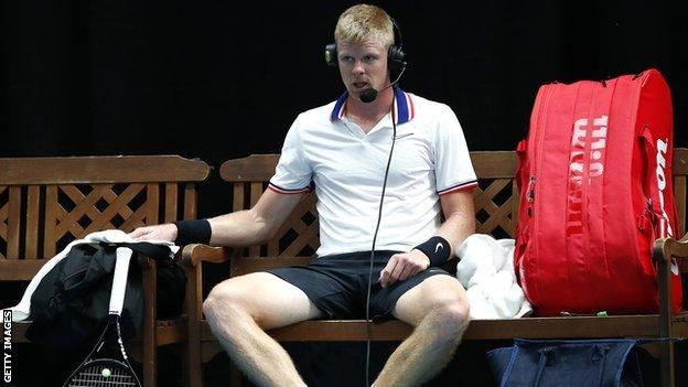 Kyle Edmund wears a headset to talk to television commentators