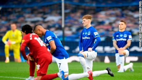 Players and officials take a knee in support of the Black Lives Matter movement  before the Merseyside derby between Everton and Liverpool at Goodison Park.