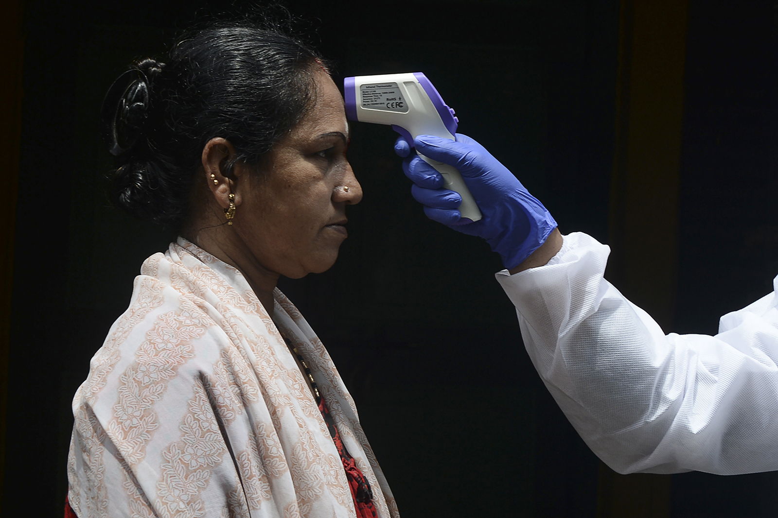 A doctor checks a woman's temperature at her residence during a government-imposed lockdown in Chennai, India, on June 29.
