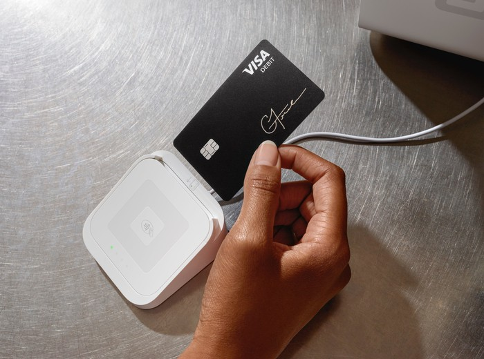 A consumer placing their Cash Card into a Square point-of-sale device.