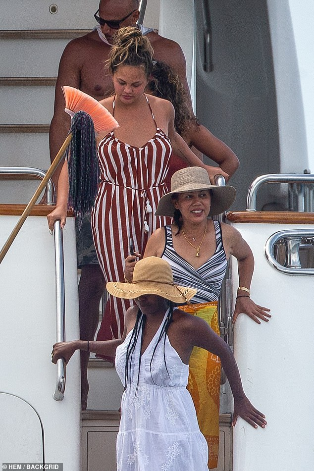 Fun on the high seas:The 5ft9in star was chic as she went bra and swimsuit free under a maroon and white striped jumpsuit that had a V necklace, thin straps and a belt with white tassels. Teigen chose to roll up the hems
