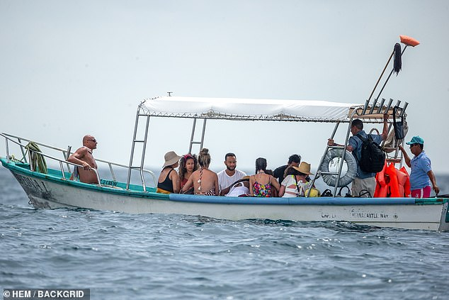 Off the yacht: They were seen in a smaller boat as they made their way back to land
