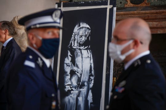 A recovered stolen artwork by British artist Banksy, depicting a young female figure with a mournful expression, that was painted as a tribute to the victims of the 2015 terror attacks at the Bataclan music hall in Paris, is shown during a ceremony at the French Embassy in Rome on July 14, 2020.