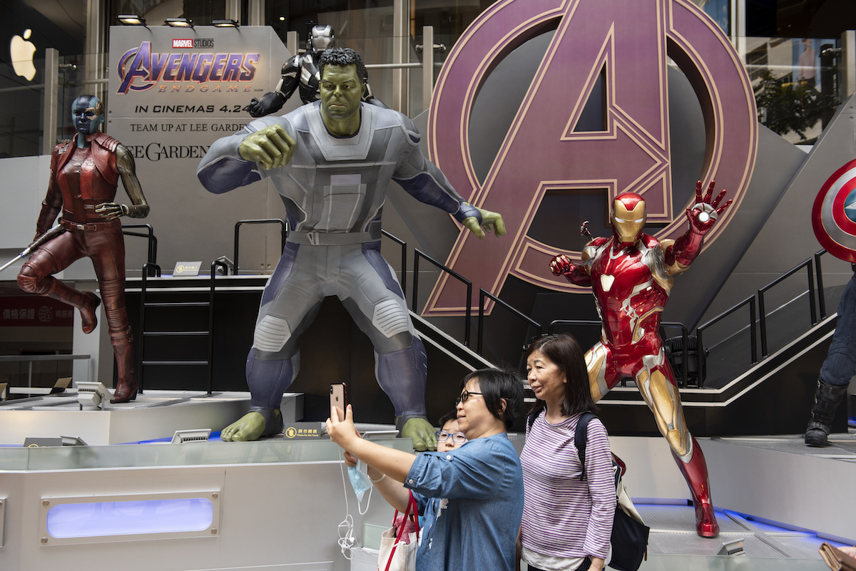 Pedestrians taking a selfie with Marvel figures
