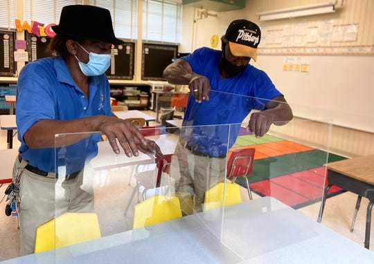 Tommy Croft and Eddie Ford install plexiglass dividers on desks in a classroom at Oakland Heights Elementary School in Meridian, Miss.