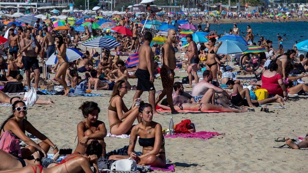 Police close down packed Barcelona beach amid virus spike