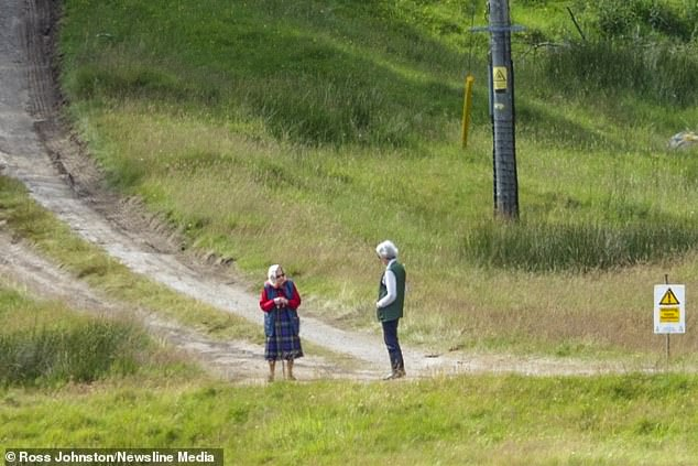 The monarch cut a casual figure in a red top, gilet and tartan skirt as she took her beloved Dorgis, Vulcan and Candy, for a walk