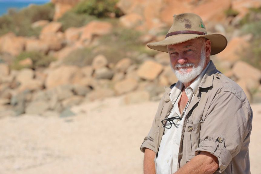 A man in an Akubra hat stands in the foreground of a rocky landscape