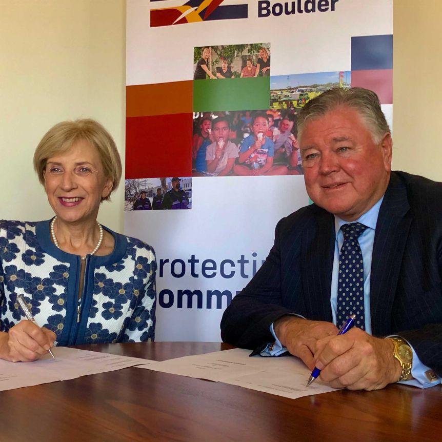 Lynas CEO Amanda Lacaze and City of Kalgoorlie-Boulder CEO John Walker sign a document.