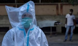 A medical worker wears personal protective equipment and a plastic bag over his head in Bhagalpur, Bihar, India, 27 July 2020.