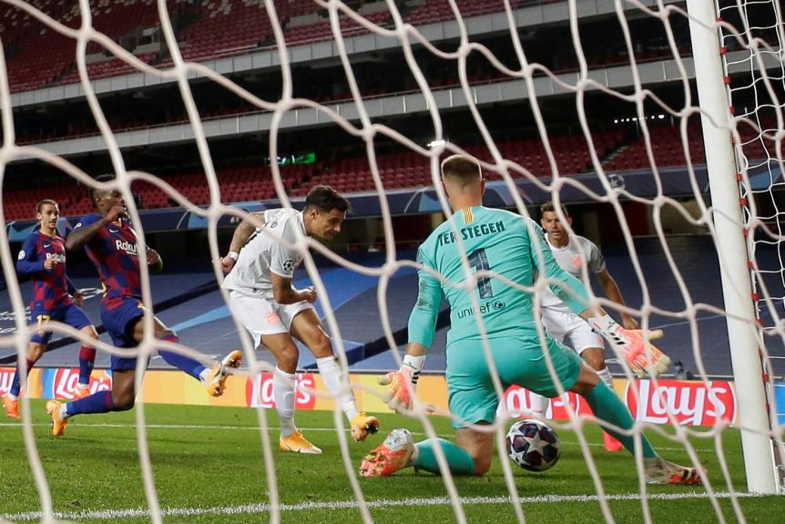 With the goal netting in the foreground, Philippe Coutinho kicks the ball toward goal as barcelona defenders surround him