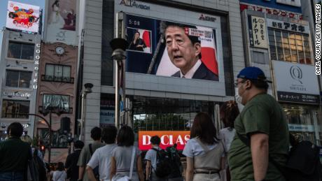 People watch Abe's press conference in Tokyo on Friday.