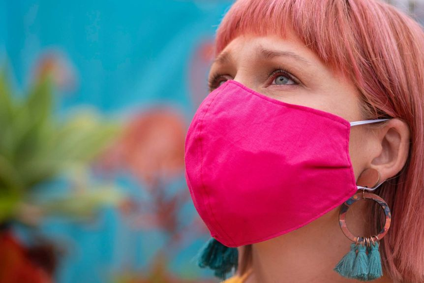 A close up image of a woman wearing a bright pink cloth face mask.