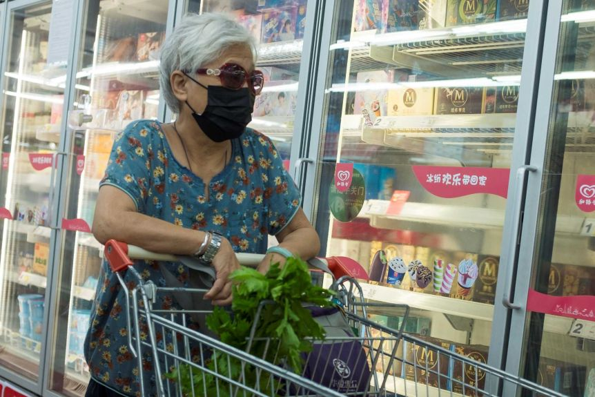 Grey-haired woman wearing black mask, looking at groceries