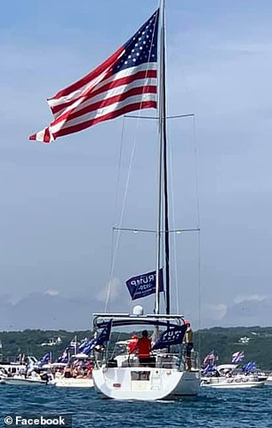 Boat sails by waving 2020 Trump flags during the parade