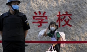 A student wears a face mask to help curb the spread of coronavirus waves alongside a masked security guard as she arrives at a primary school in Beijing, Monday, September 7, 2020.