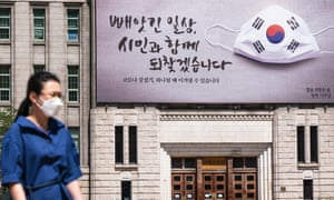 A woman wearing a face mask as a precaution walks under a campaign banner on the wall of Seoul City Hall, South Korea.