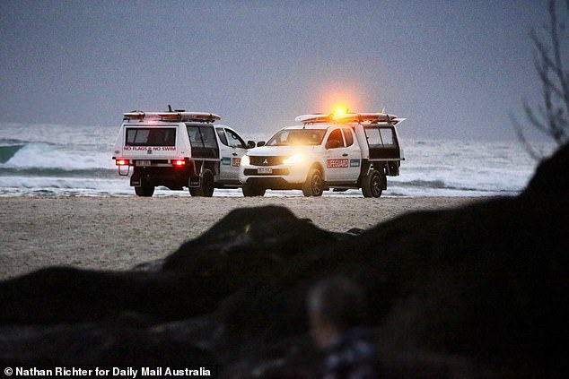 Two rescue trucks stopped on the sands of Greenmount Beach as the sun rose on Wednesday morning