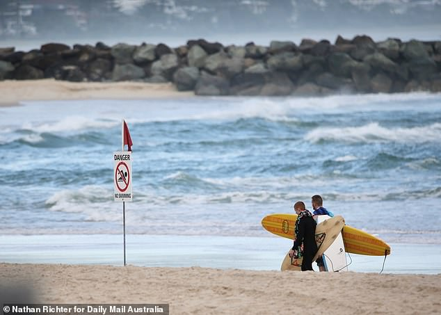 Two surfers are seen walking near a sign