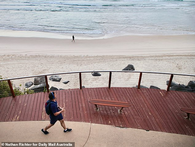 A man walks along a boardwalk as Greenmount Beach closes on Wednesday morning
