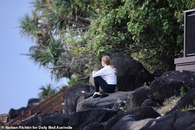 A woman sits on a rock overlooking the water at Greenmount Beach on Wednesday morning