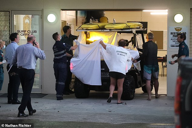 Pictured: Members of the public and paramedics cover the victim, who was treated on the back of the beach cart