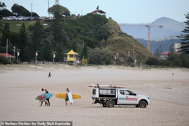 A rescue cart is seen parked on the sand as surfers leave Greenmount Beach on Wednesday morning