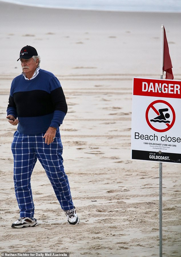 A man walks past a sign announcing the closure of Greenmount Beach on Wednesday morning