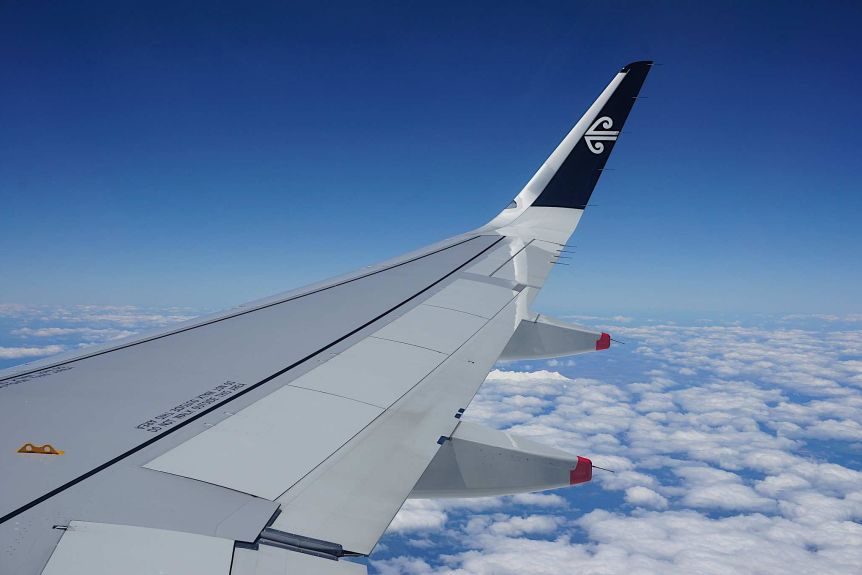 You're looking at the wing of an airplane flying over scattered clouds across a blue sky with the Air New Zealand logo on the tip.