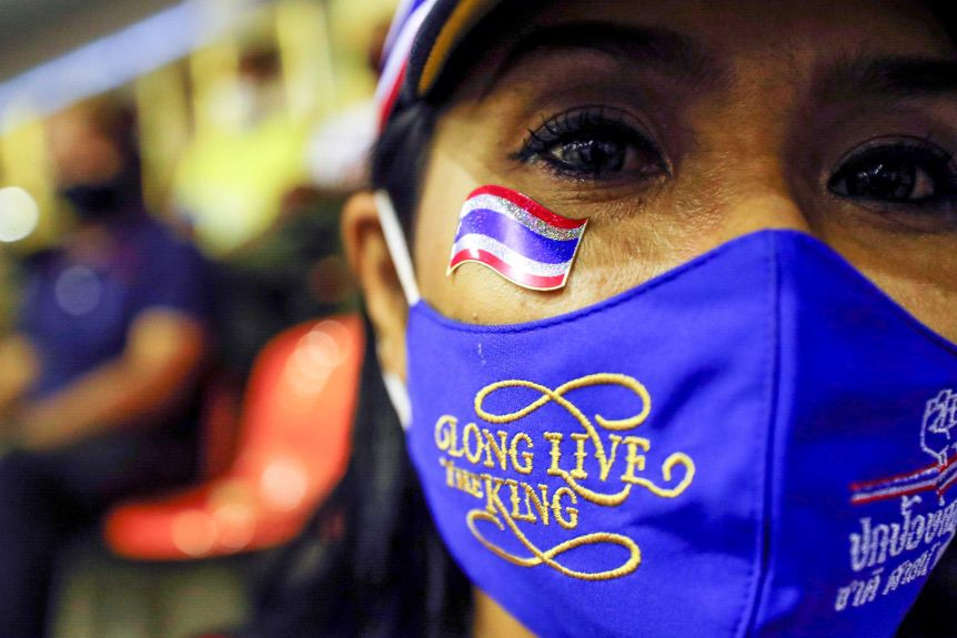 "A woman wearing a face mask reads: ""Long live the king"""