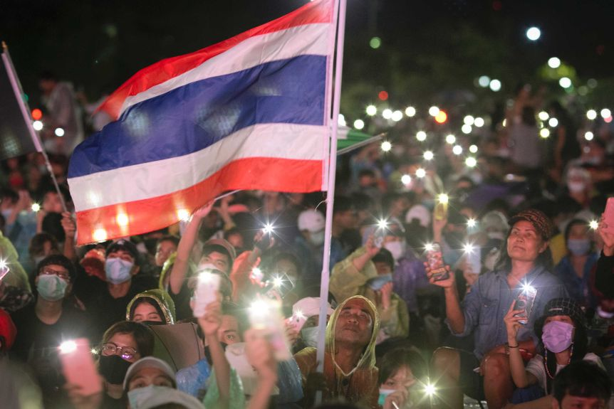 People sitting in rain coats waving smartphone lights and the Thai flag at night