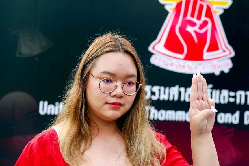 A young Thai woman raises three fingers