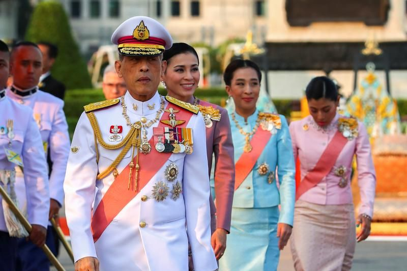 Thailand's King Maha Vajiralongkorn walks in traditional white attire while parading.