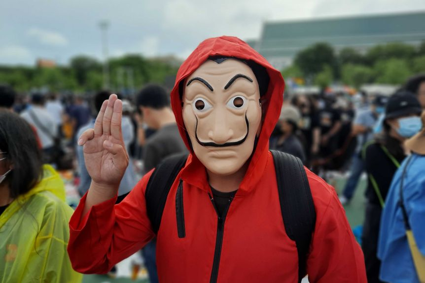 A person in a red hoodie and an anonymous mask greets three fingers.