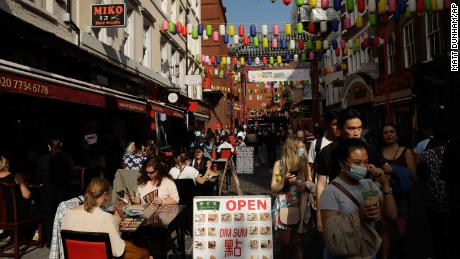 People are sitting outside in Chinatown, central London, on Saturday. The United Kingdom has imposed a curfew at 10 pm on bars and restaurants.