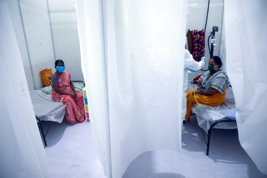 Two Indian women are in hospital rooms, separated by a white curtain