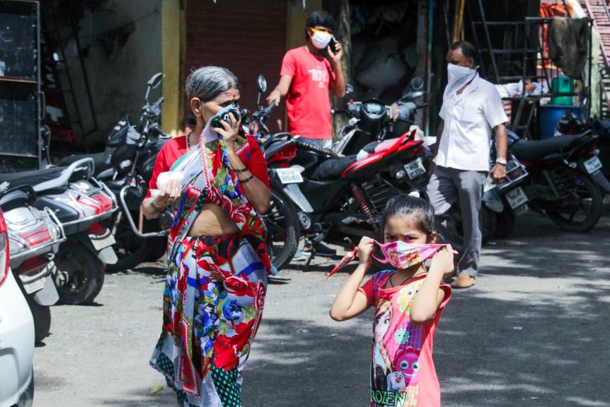 A young girl in a Frozen dress and mask walks down the street next to an older woman wearing a sari