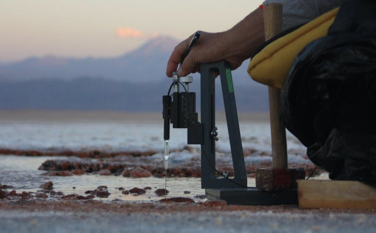Peter Fisher uses field equipment to measure the chemical composition of purple microbial mats.