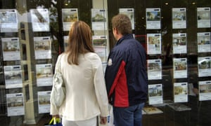 Young men are looking at the real estate agent window