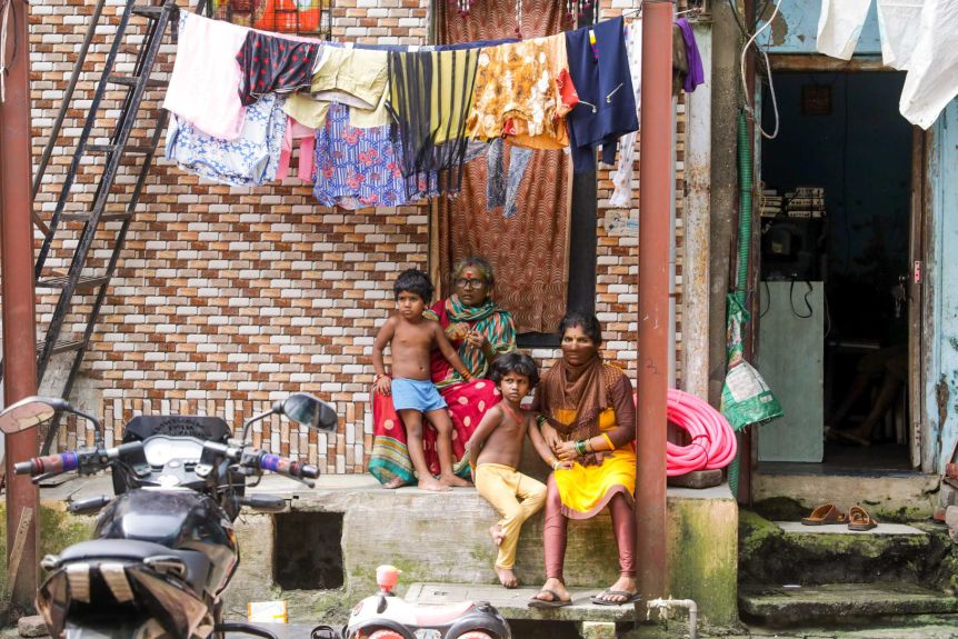 A grandmother, mother and two young children are sitting on a slope under the washing line