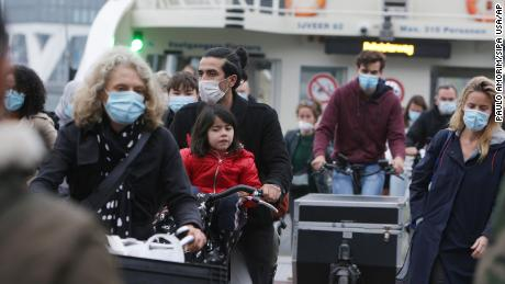 Locals wear masks on a ferry on the IJ River in Amsterdam as face coverings have become mandatory in the Netherlands.