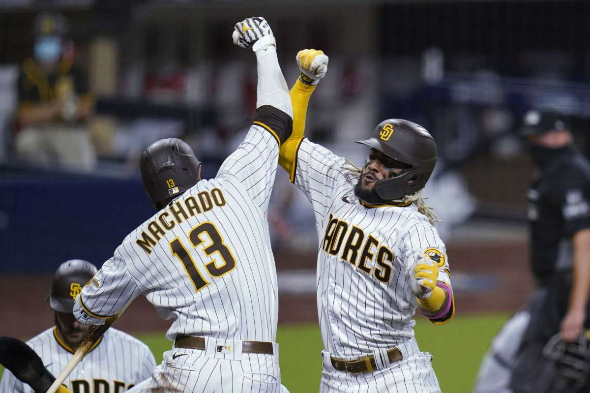 Fernando Tatis Jr. of San Diego Padres, right, was congratulated by Mane Machado, left, after he scored three rounds at home during the sixth game of the second game of the National League Baseball Series against the St. Louis Cardinals.  Thursday, October 1, 2020, in San Diego.