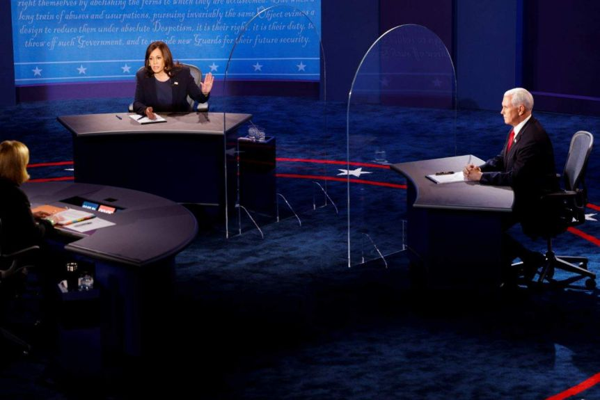 Kamala Harris and Mike Pence sit behind glass shields separating their desks on the debate stage