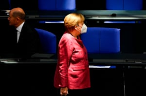 Angela Merkel wears a face mask as she walks past Finance Minister and Deputy Chancellor Olaf Schultz to take her seat in the Bundestag.