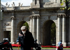 A man wears a face mask in front of Puerta de Alcala, Madrid.