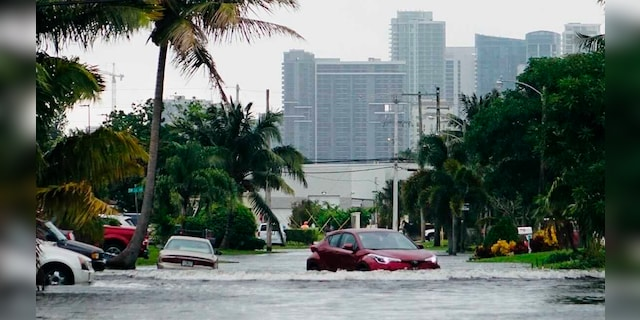 A car drives down a flooded street in the Melrose Manors neighborhood west of downtown Fort Lauderdale on Monday, November 9, 2020.