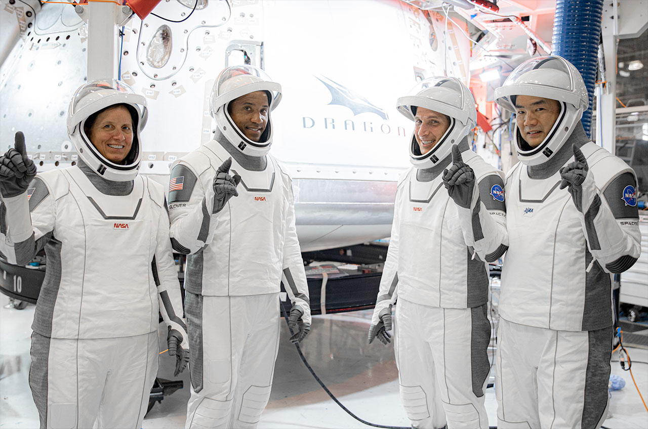 """SpaceX's Crew-1 astronauts, including NASA astronauts Shannon Walker, Victor Glover, Michael Hopkins, and JAXA astronaut Soichi Noguchi, stand in front of their Dragon capsule, """"Flexibility,"""" At SpaceX headquarters in Hawthorne, California."""