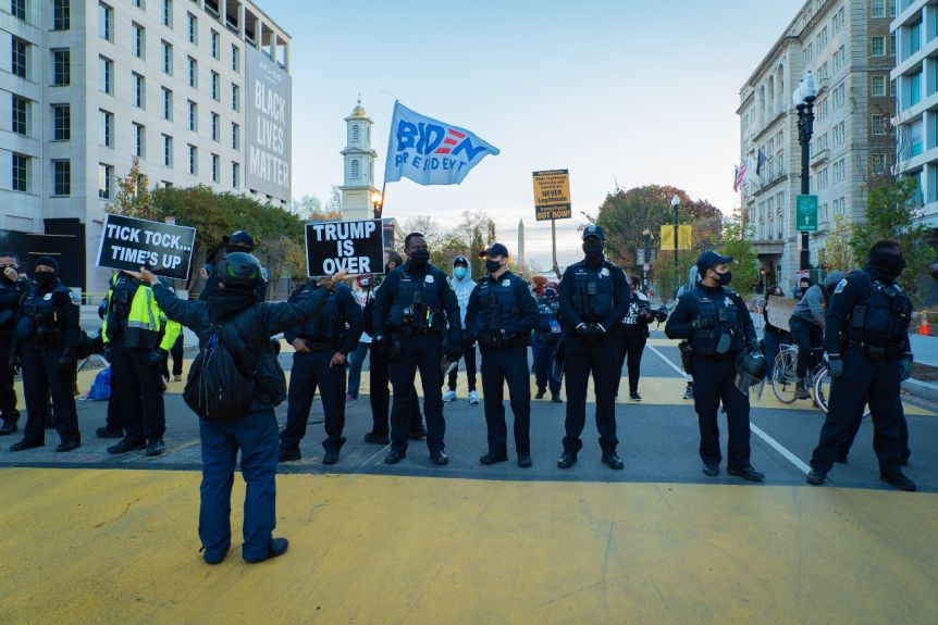 A person raises black banners in front of a row of police officers